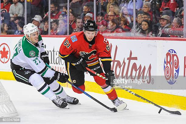 Brett Kulak of the Calgary Flames chases the puck against Adam Cracknell of the Dallas Stars during an NHL game at Scotiabank Saddledome on November...