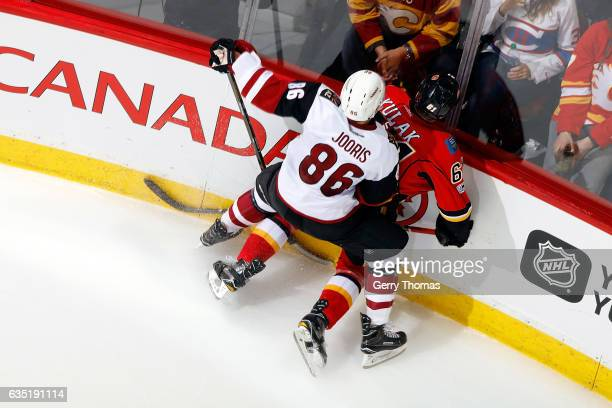 Brett Kulak of the Calgary Flames is checked by Josh Jooris of the Arizona Coyotes during an NHL game on February 13 2017 at the Scotiabank...