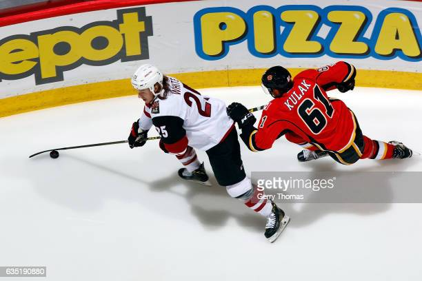 Brett Kulak of the Calgary Flames skates against Ryan White of the Arizona Coyotes during an NHL game on February 13 2017 at the Scotiabank...