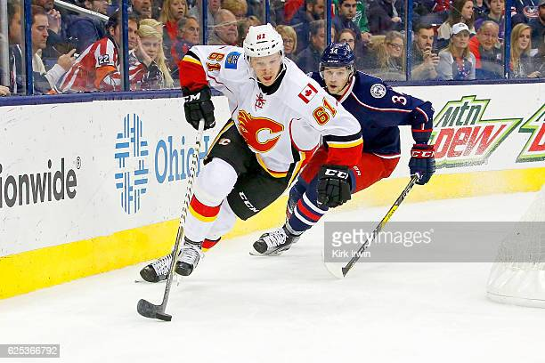 Brett Kulak of the Calgary Flames skates the puck away from Josh Anderson of the Columbus Blue Jackets during the second perio on November 23 2016 at...