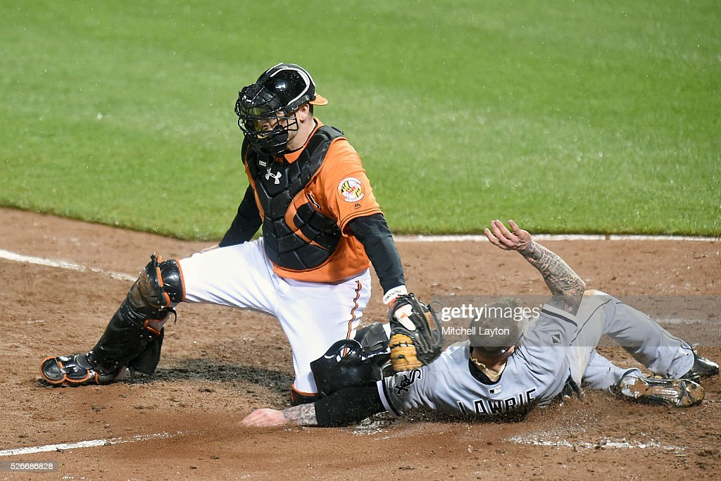 Brett Lawrie #15 of the Chicago White Sox beats the tag by Matt Wieters #32 of the Baltimore Orioles on a Austin Jackson #10 not pictured) single in the seventh inning during a baseball game at Oriole Park at Camden yards on April 30, 2016 in Baltimore, Maryland.