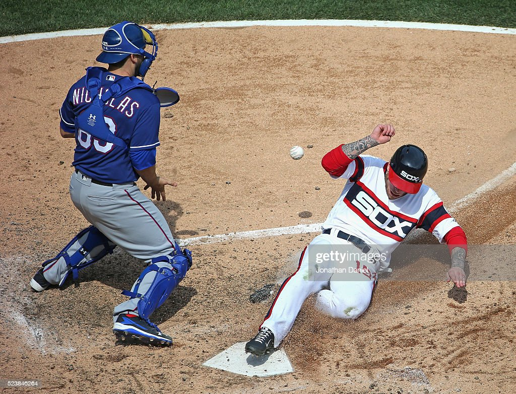 Brett Lawrie of the Chicago White Sox slides across the plate to score a run ahead of the throw to Brett Nicholas of the Texas Rangers in the 5th...
