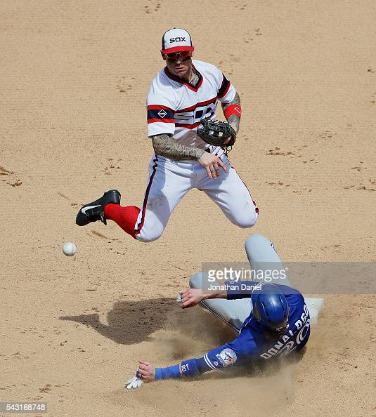 Brett Lawrie of the Chicago White Sox turns a double play over Josh Donaldson of the Toronto Blue Jays in the 7th inning at US Cellular Field on June...