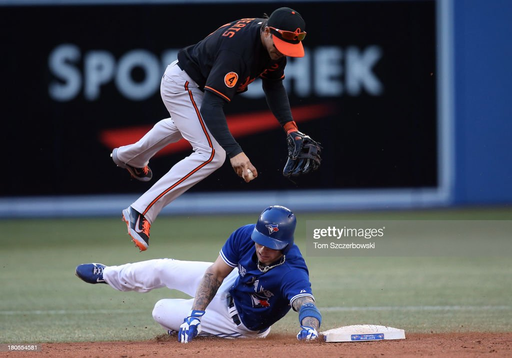 <a gi-track='captionPersonalityLinkClicked' href=/galleries/search?phrase=Brett+Lawrie&family=editorial&specificpeople=5496694 ng-click='$event.stopPropagation()'>Brett Lawrie</a> #13 of the Toronto Blue Jays breaks up a double play in the sixth inning during MLB game action as he takes out Brian Roberts #1 of the Baltimore Orioles on September 14, 2013 at Rogers Centre in Toronto, Ontario, Canada.
