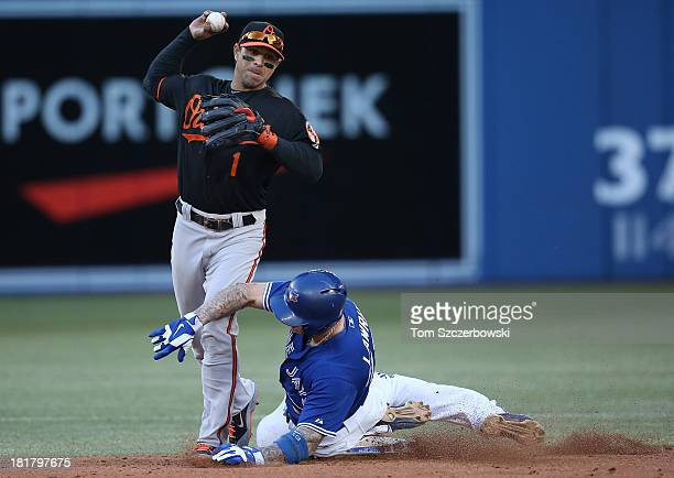 Brett Lawrie of the Toronto Blue Jays breaks up a double play in the sixth inning during MLB game action as he takes out Brian Roberts of the...