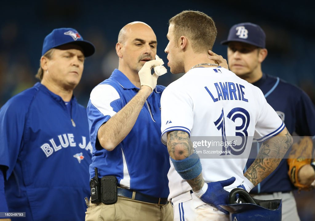 <a gi-track='captionPersonalityLinkClicked' href=/galleries/search?phrase=Brett+Lawrie&family=editorial&specificpeople=5496694 ng-click='$event.stopPropagation()'>Brett Lawrie</a> #13 of the Toronto Blue Jays is examined by trainer George Poulis and manager John Gibbons #5 during MLB game action as Evan Longoria #3 of the Tampa Bay Rays looks on on September 27, 2013 at Rogers Centre in Toronto, Ontario, Canada.
