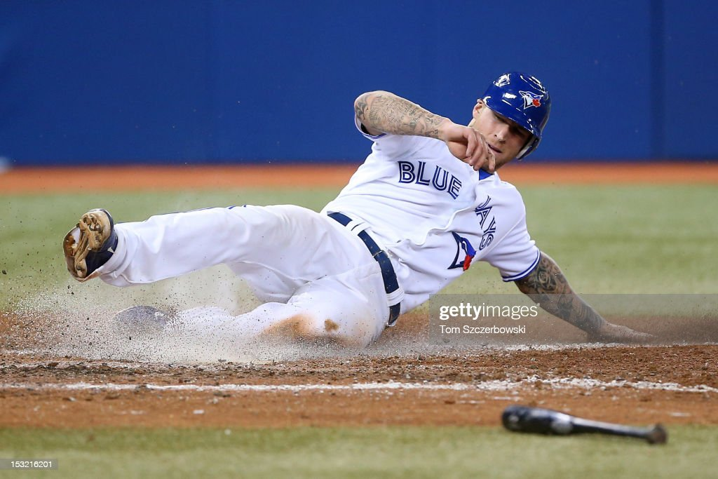 <a gi-track='captionPersonalityLinkClicked' href=/galleries/search?phrase=Brett+Lawrie&family=editorial&specificpeople=5496694 ng-click='$event.stopPropagation()'>Brett Lawrie</a> #13 of the Toronto Blue Jays slides across home plate in the seventh inning to score a run during MLB game action against the Minnesota Twins on October 1, 2012 at Rogers Centre in Toronto, Ontario, Canada.