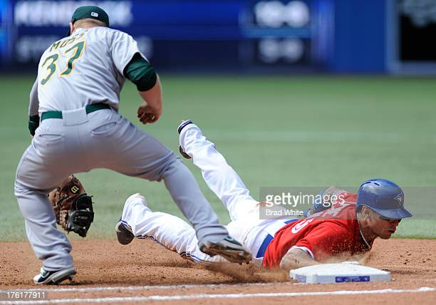 Brett Lawrie of the Toronto Blue Jays slides back into first base as Brandon Moss of the Oakland Athletics covers the bag during MLB game action...