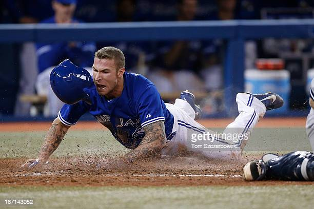 Brett Lawrie of the Toronto Blue Jays slides safely into home plate to score a run in the sixth inning on an RBI single by Melky Cabrera during MLB...