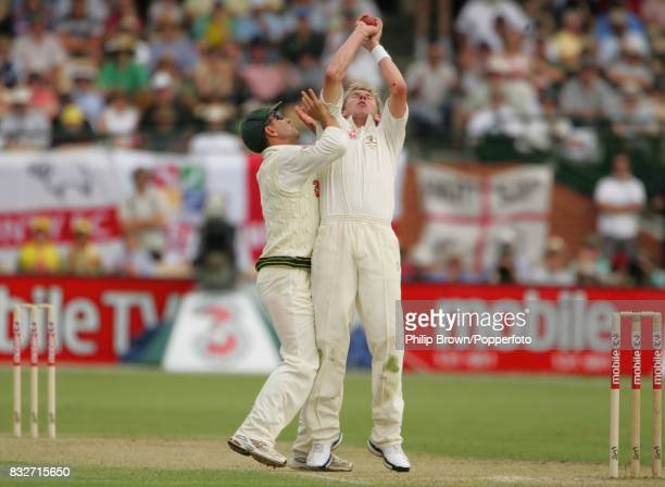 Brett Lee of Australia holds on to the catch to dismiss England batsman Ian Bell for 60 runs as Justin Langer collides with him during day one of the...