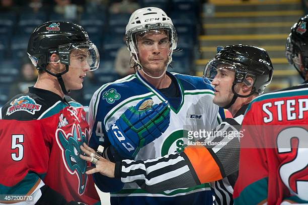 Brett Lernout of Swift Current Broncos stands between an official and Dalton Yorke of Kelowna Rockets on October 7 2014 at Prospera Place in Kelowna...