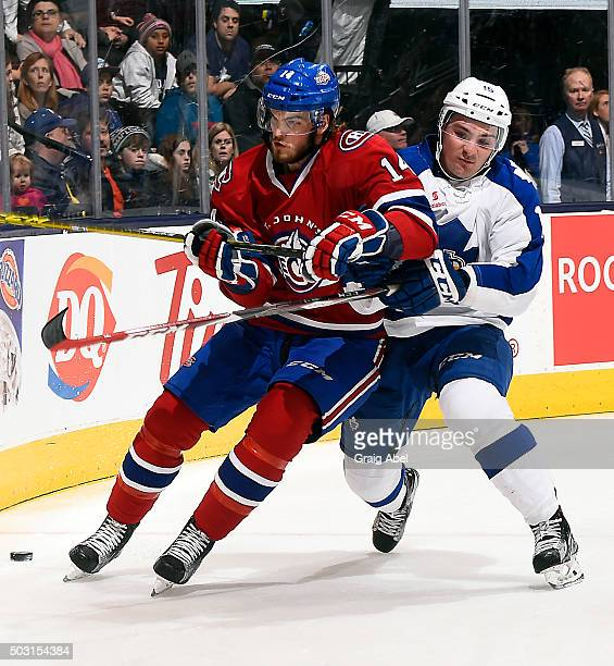 Brett Lernout of the St Johns IceCaps is held up by Sam Carrick of the Toronto Marlies during AHL game action on December 26 2015 at Air Canada...