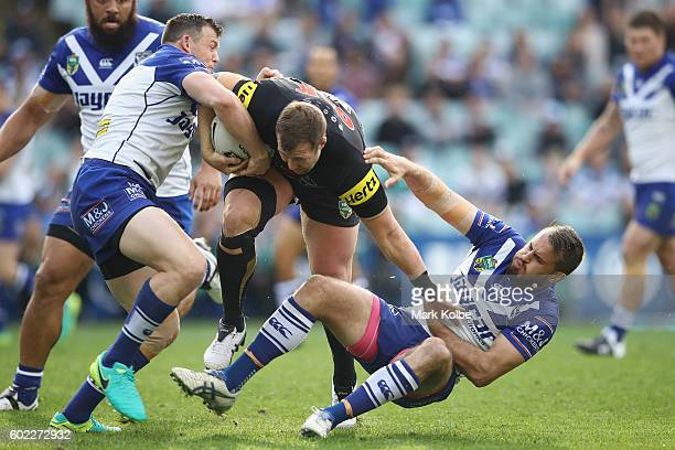 Brett Morris and Josh Reynolds of the Bulldogs tackle Trent Merrin of the Panthers during the NRL Elimination Final match between the Penrith...