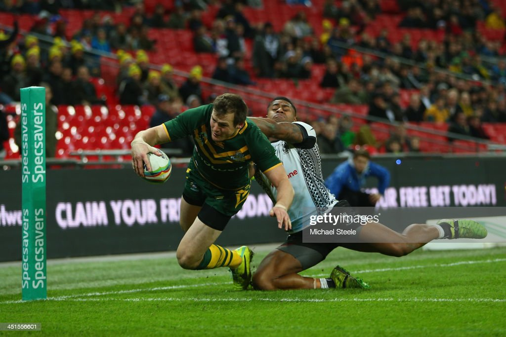 Brett Morris of Australia scores a try as Kevin Naiqama of Fiji challenges during the Rugby League World Cup Semi Final match between Australia and...