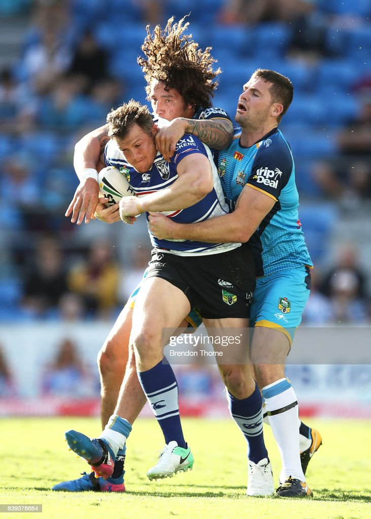 Brett Morris of the Bulldogs is tackled by Kevin Proctor and Anthony Don of the Titans during the round 25 NRL match between the Gold Coast Titans and the Canterbury Bulldogs at Cbus Super Stadium on August 26, 2017 in Gold Coast, Australia.