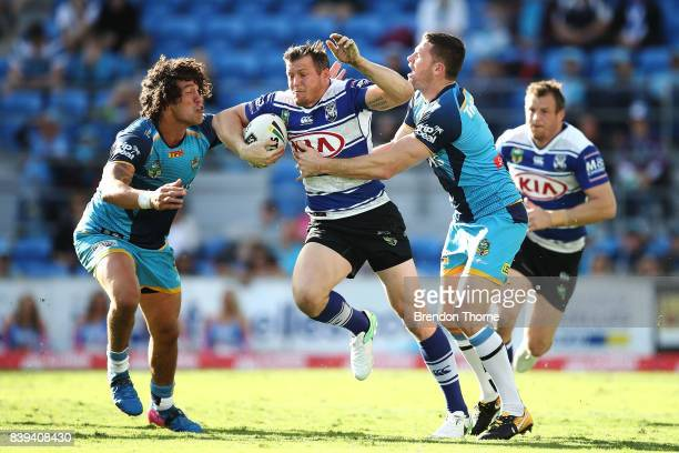 Brett Morris of the Bulldogs is tackled by Kevin Proctor and Anthony Don of the Titans during the round 25 NRL match between the Gold Coast Titans...
