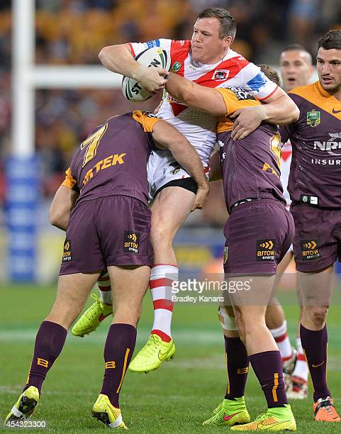 Brett Morris of the Dragons is picked up by the defence during the round 25 NRL match between the Brisbane Broncos and the St George Illawarra...