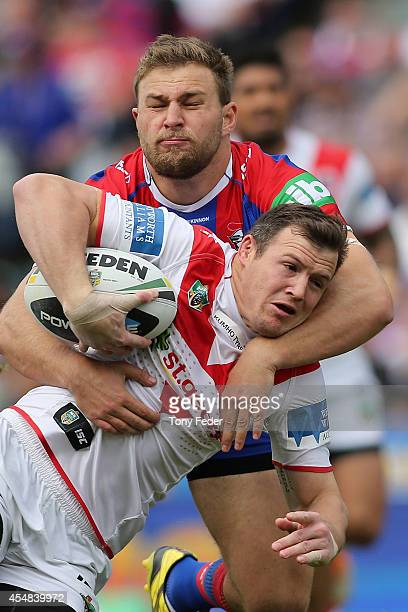 Brett Morris of the Dragons is tackled by Robbie Rochow of the Knights during the round 26 NRL match between the Newcastle Knights and the St George...