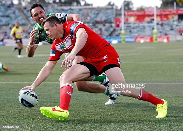 Brett Morris of the Dragons scores a try during the round 23 NRL match between the Canberra Raiders and the St George Illawarra Dragons at GIO...