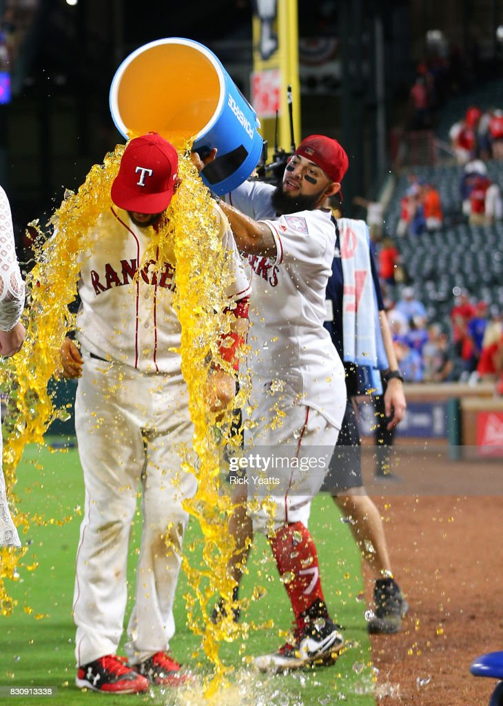 Brett Nicholas #6 of the Texas Rangers gets the cooler dumped on him by Rougned Odor #12 at the conclusion of the game against the Houston Astros at Globe Life Park in Arlington on August 12, 2017 in Arlington, Texas.