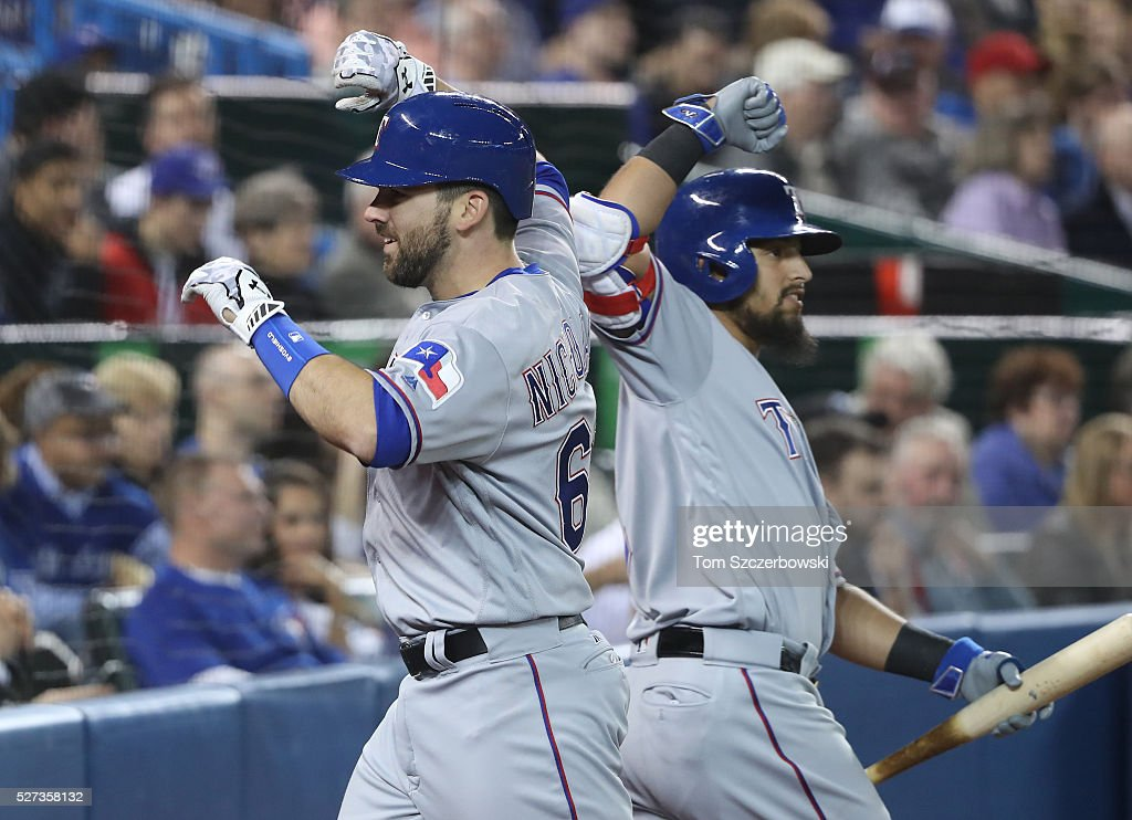 Brett Nicholas #63 of the Texas Rangers is congratulated by Rougned Odor #12 after hitting a solo home run in the third inning during MLB game action against the Toronto Blue Jays on May 2, 2016 at Rogers Centre in Toronto, Ontario, Canada.