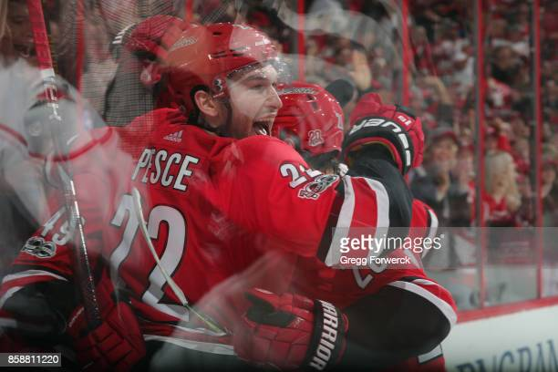 Brett Pesce and Sebastian Aho of the Carolina Hurricanes surround goal scorer Victor Rask in the third period of an NHL game against the Minnesota...