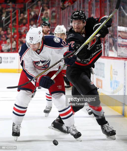 Brett Pesce of the Carolina Hurricanes and Brandon Saad of the Columbus Blue Jackets battle for the puck during an NHL game on March 30 2017 at PNC...