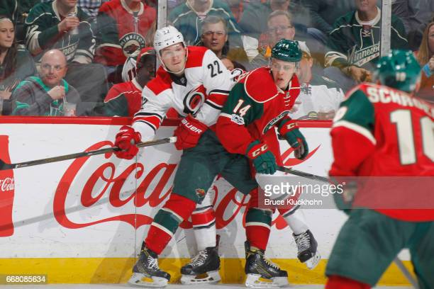 Brett Pesce of the Carolina Hurricanes and Joel Eriksson Ek of the Minnesota Wild battle for the puck along the boards during the game on April 4...