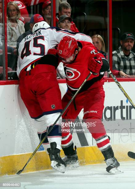 Brett Pesce of the Carolina Hurricanes and Lukas Sedlak of the Columbus Blue Jackets meet along the boards during an NHL game on October 10 2017 at...