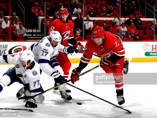 Brett Pesce of the Carolina Hurricanes battles for a loose puck near the crease with Alex Killorn of the Tampa Bay Lightning Victor Hedman during an...