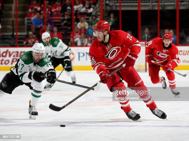 Brett Pesce of the Carolina Hurricanes carries the puck and has his stick lifted by Jason Dickinson of the Dallas Stars during an NHL game on April 1...