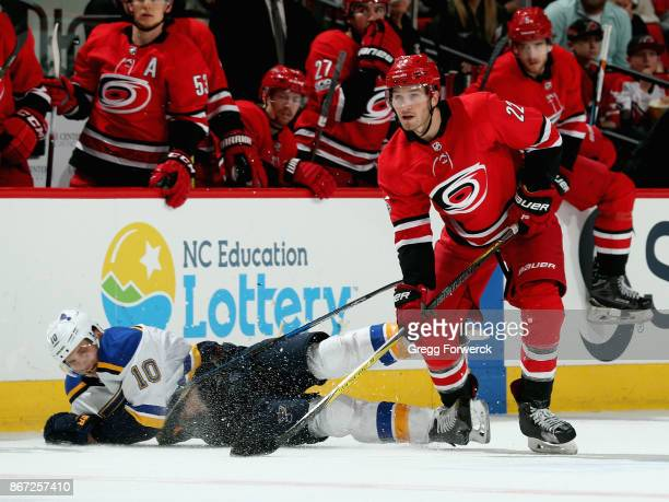 Brett Pesce of the Carolina Hurricanes collects the puck as Brayden Schenn of the St Louis Blues falls to the ice during an NHL game on October 27...