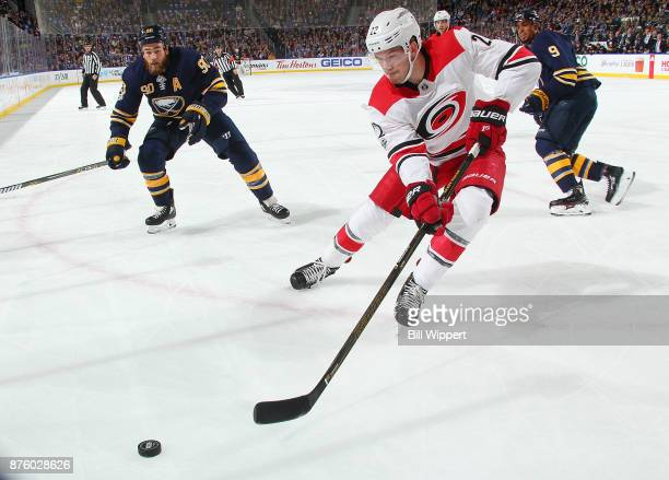 Brett Pesce of the Carolina Hurricanes controls the puck against Ryan O'Reilly and Evander Kane of the Buffalo Sabres during an NHL game on November...