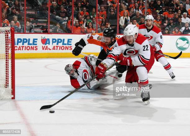 Brett Pesce of the Carolina Hurricanes controls the puck ahead of an attacking Sean Courturier of the Philadelphia Flyers on March 19 2017 at the...