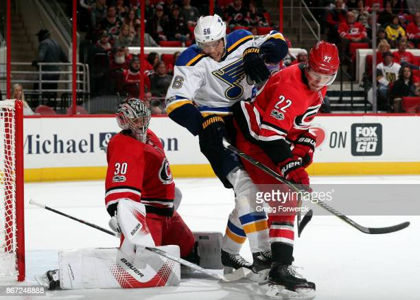 Brett Pesce of the Carolina Hurricanes defends Magnus Paajarvi of the St Louis Blues as Cam Ward reacts to a shot during an NHL game on October 27...