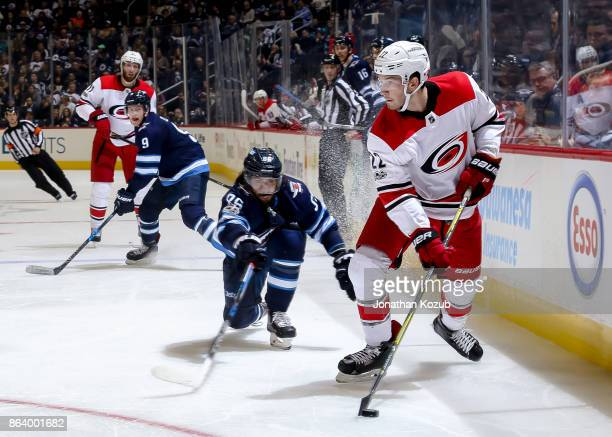 Brett Pesce of the Carolina Hurricanes plays the puck down the ice as Mathieu Perreault of the Winnipeg Jets gives chase during second period action...