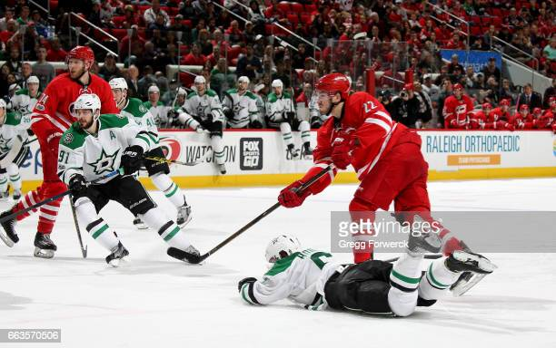 Brett Pesce of the Carolina Hurricanes shoots the puck past the defense of Julius Honka of the Dallas Stars during an NHL game on April 1 2017 at PNC...