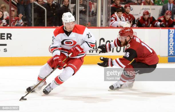 Brett Pesce of the Carolina Hurricanes skates with the puck while being defeded by Max Domi of the Arizona Coyotes during the second period at Gila...