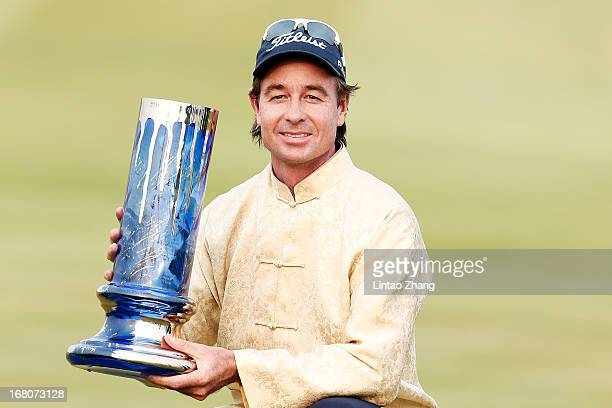Brett Rumford of Australia celebrates with the trophy after winning the final round of the Volvo China Open at Binhai Lake Golf Course on May 5 2013...