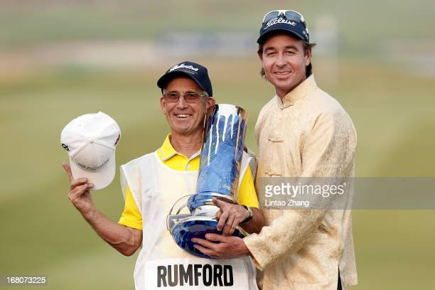Brett Rumford of Australia holding the winner's trophy poses with his caddie after winning the final round of the Volvo China Open at Binhai Lake...