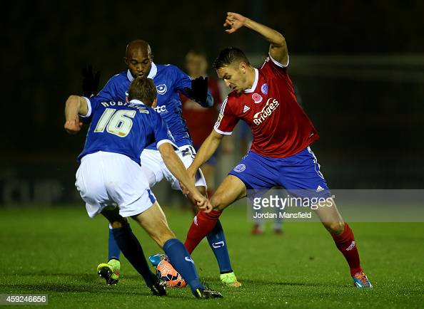 Brett Williams of Aldershot is tackled by Nigel Atangana and Paul Robinson of Portsmouth during the FA Cup First Round Replay match between Aldershot...