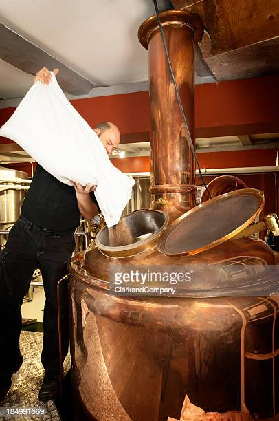 Brewer Adding Malt to a Copper Mash Tun or Kettle