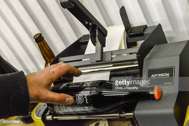 A brewer applies labels by hand to Megawatt Double IPA at inner city craft beer makers Brixton Brewery on December 8 2015 in London England Located...