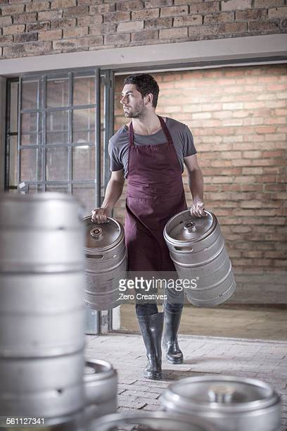 Brewer carrying two kegs of beer