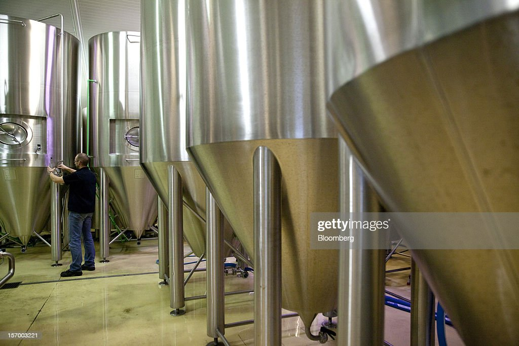 A brewer checks the beer fermentation process in double-walled tanks at the Brasserie Saint Germain brewery in Aix-Noulette, in France, on Monday, Nov. 26, 2012. Producers of beer in France, for instance, say any development plans they had have been 'nipped in the bud' by Hollande's plan to boost the tax on the drink next year. Photographer: Balint Porneczi/Bloomberg via Getty Images