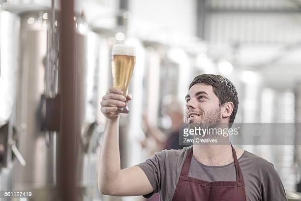 Brewer in brewery holding up a glass of beer