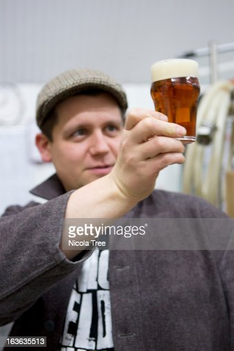 brewer tasting and checking beers clarity : Stock Photo