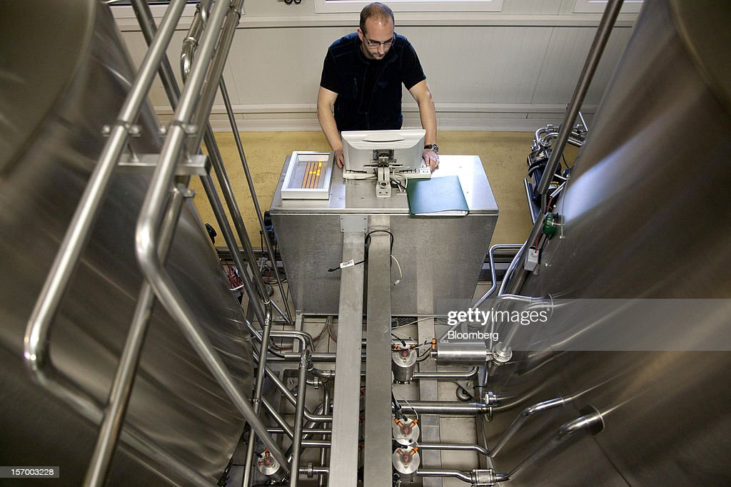 A brewer uses a computer to regulate the fermentation process at the Brasserie Saint Germain brewery during the beer manufacturing process in Aix-Noulette, in France, on Monday, Nov. 26, 2012. Producers of beer in France, for instance, say any development plans they had have been 'nipped in the bud' by Hollande's plan to boost the tax on the drink next year. Photographer: Balint Porneczi/Bloomberg via Getty Images