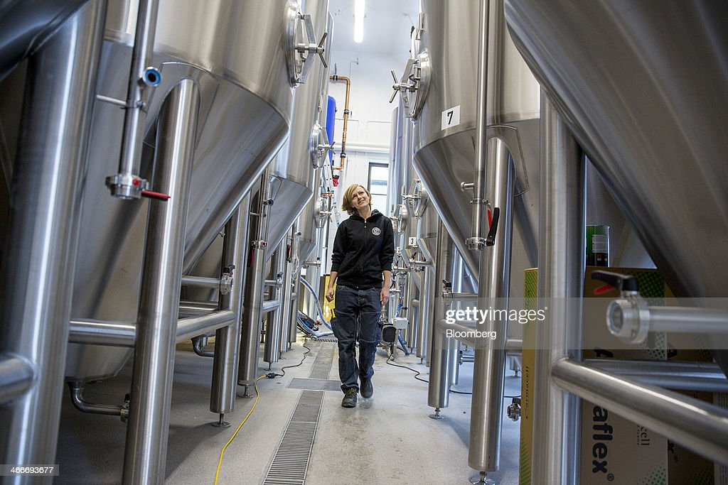 A brewer walks past beer fermentation tanks at the 'New Carnegie Brewery,' also known as Nya Carnegibryggeriet, operated by Brooklyn Brewery Corp. in collaboration with D. Carnegie & Co., the Swedish unit of Carlsberg A/S, stands in Stockholm, Sweden, on Friday, Jan. 31, 2014. Brooklyn has teamed up with the Swedish unit of Carlsberg A/S, D. Carnegie & Co. and a few private investors to create 'The New Carnegie Brewery,' with an annual capacity of 1 million liters. Photographer: Casper Hedberg/Bloomberg via Getty Images