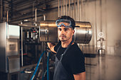 Portrait of male brewer with keg at brewery factory. Young man holding a metal beer container on shoulder at warehouse.